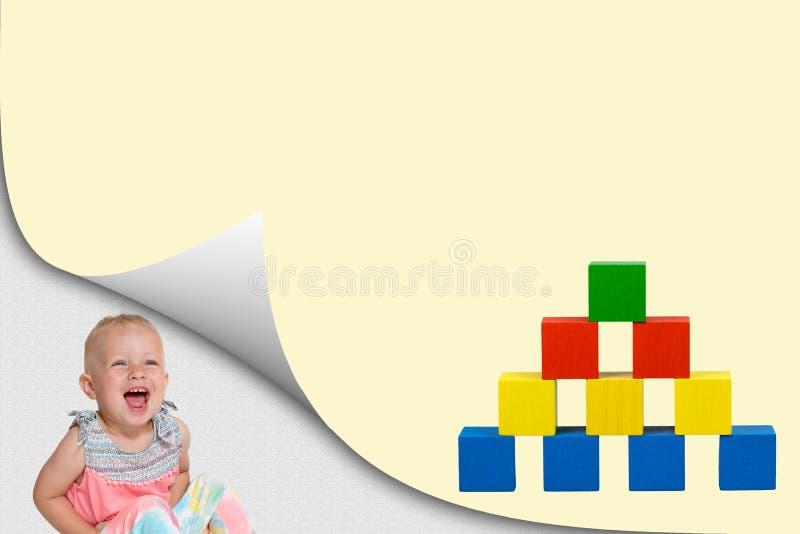 Γελώντας κορίτσι μικρών παιδιών και πυραμίδα των ξύλινων κύβων παιχνι στοκ εικόνα με δικαίωμα ελεύθερης χρήσης