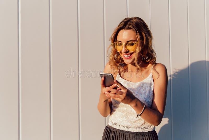 Γελώντας κορίτσι που εξετάζει την κινητή τηλεφωνική οθόνη, που στέκεται υπαίθρια στοκ φωτογραφία με δικαίωμα ελεύθερης χρήσης