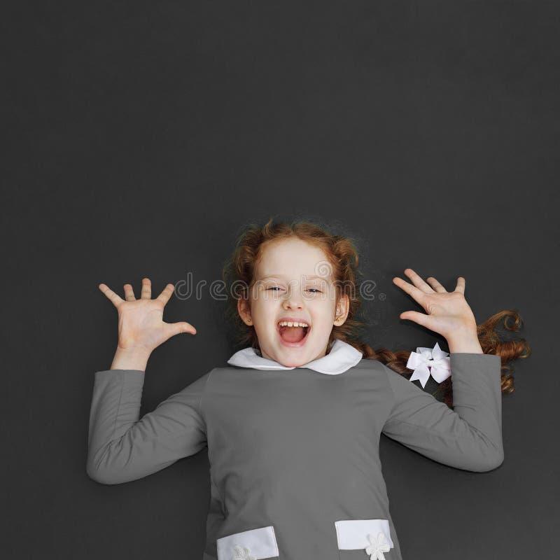 Γελώντας μικρό κορίτσι που στέκεται κοντά στον πίνακα στοκ εικόνες με δικαίωμα ελεύθερης χρήσης