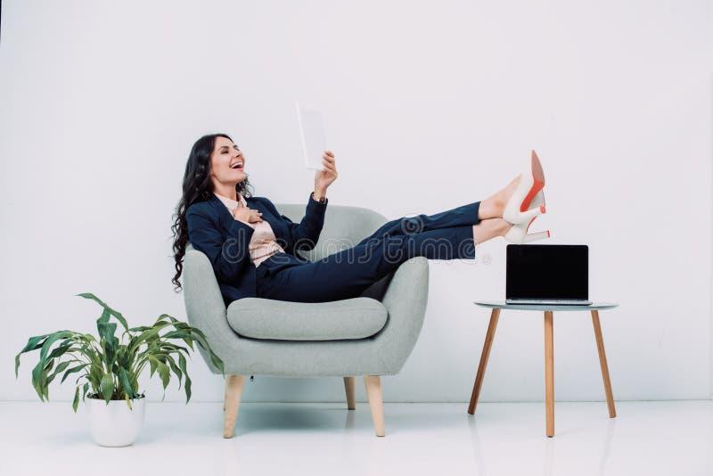 γελώντας νέα επιχειρηματίας που χρησιμοποιεί την ταμπλέτα χαλαρώνοντας στοκ φωτογραφία με δικαίωμα ελεύθερης χρήσης