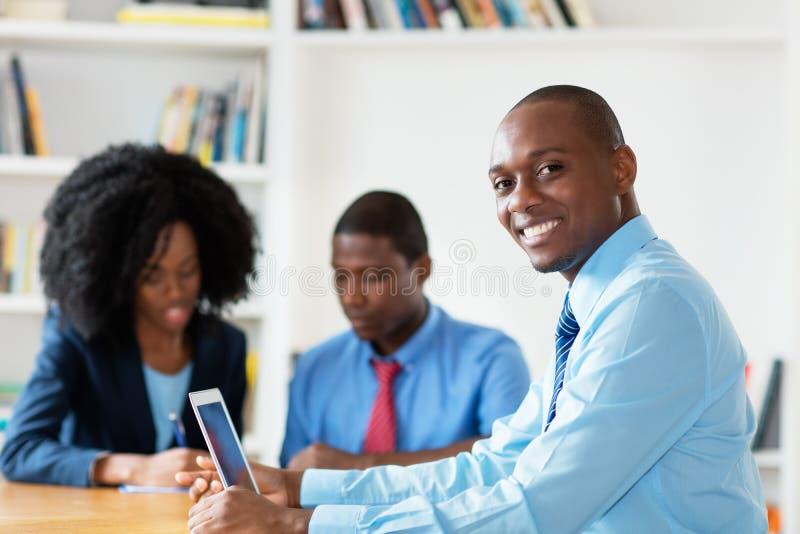 Γελώντας οικονομικός σύμβουλος αφροαμερικάνων με την επιχειρησιακή ομάδα στοκ εικόνα με δικαίωμα ελεύθερης χρήσης