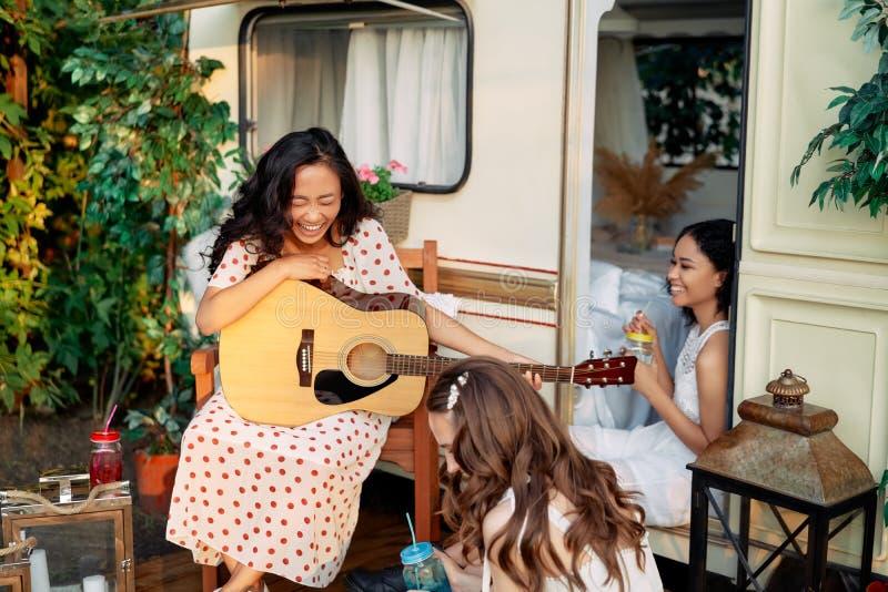 Γελώντας χαρούμενες γυναίκες με κιθάρα διασκεδάζουν έξω, κοντά στο τροχόσπιτο τους κατά τη διάρκεια του καλοκαιριού στοκ φωτογραφία