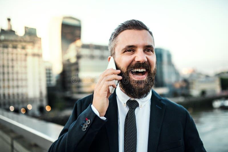 Γελώντας hipster επιχειρηματίας με το smartphone στην πόλη, που κάνει ένα τηλεφώνημα στοκ φωτογραφία με δικαίωμα ελεύθερης χρήσης