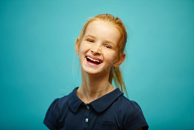 Γελώντας redhead κορίτσι παιδιών, πορτρέτο στο μπλε που απομονώνεται στοκ φωτογραφία