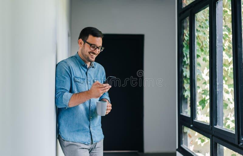 Γεμάτος αυτοπεποίθηση χαμογελαστός νεαρός χαρούμενος περιστασιακός άνδρας που κοιτάζει μέσα και χρησιμοποιεί το κινητό έξυπνο τηλ στοκ φωτογραφίες