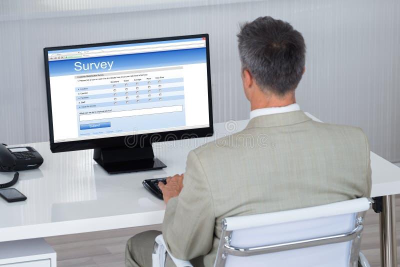 Γεμίζοντας μορφή ερευνών επιχειρηματιών στον υπολογιστή στο γραφείο στοκ φωτογραφίες με δικαίωμα ελεύθερης χρήσης