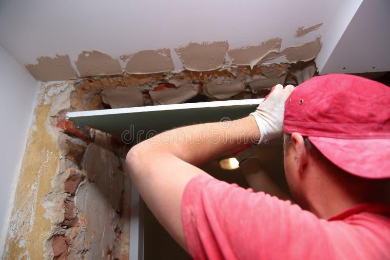 Γεμίζοντας τοίχοι και συνέλευση και να κολλήσει τους πίνακες γύψου κατά τη διάρκεια της ανακαίνισης ενός δωματίου στοκ εικόνα