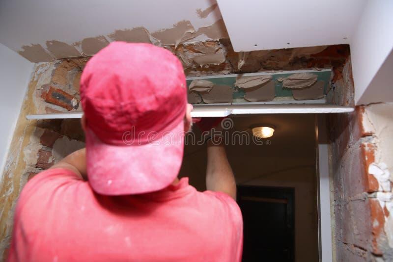 Γεμίζοντας τοίχοι και συνέλευση και να κολλήσει τους πίνακες γύψου κατά τη διάρκεια της ανακαίνισης ενός δωματίου στοκ φωτογραφία με δικαίωμα ελεύθερης χρήσης