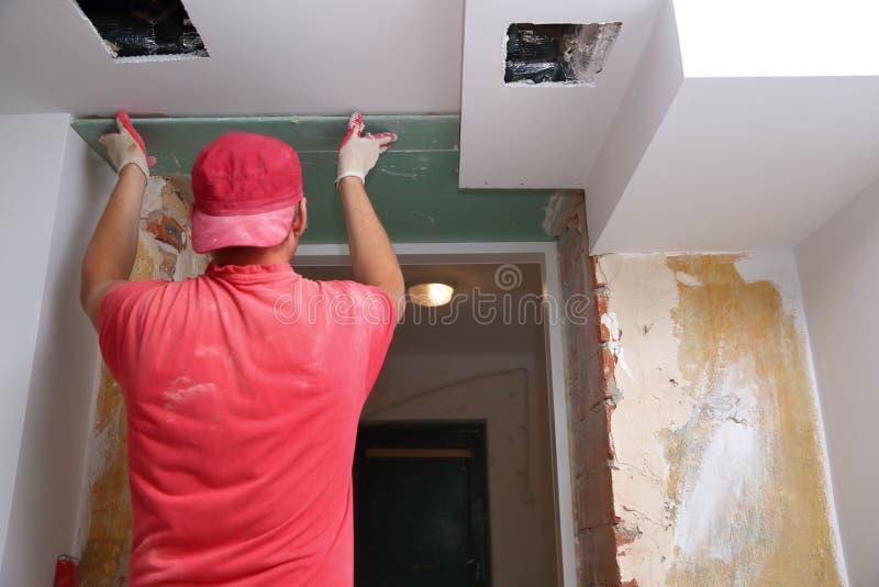 Γεμίζοντας τοίχοι και συνέλευση και να κολλήσει τους πίνακες γύψου κατά τη διάρκεια της ανακαίνισης ενός δωματίου στοκ εικόνες με δικαίωμα ελεύθερης χρήσης