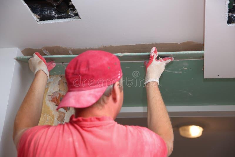 Γεμίζοντας τοίχοι και συνέλευση και να κολλήσει τους πίνακες γύψου κατά τη διάρκεια της ανακαίνισης ενός δωματίου στοκ εικόνες