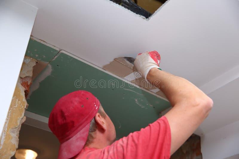 Γεμίζοντας τοίχοι και συνέλευση και να κολλήσει τους πίνακες γύψου κατά τη διάρκεια της ανακαίνισης ενός δωματίου στοκ φωτογραφίες