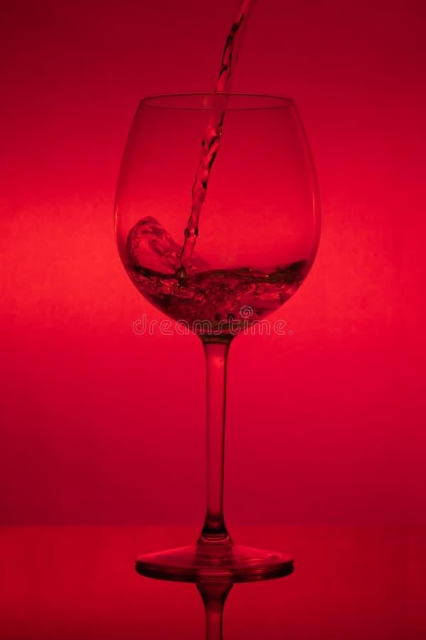 Γεμίζοντας το γυαλί, που χύνει wineglass στο κόκκινο υπόβαθρο στοκ φωτογραφία