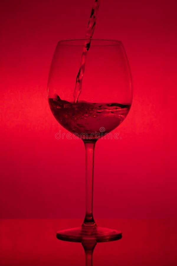 Γεμίζοντας το γυαλί, που χύνει wineglass στο κόκκινο υπόβαθρο στοκ εικόνες
