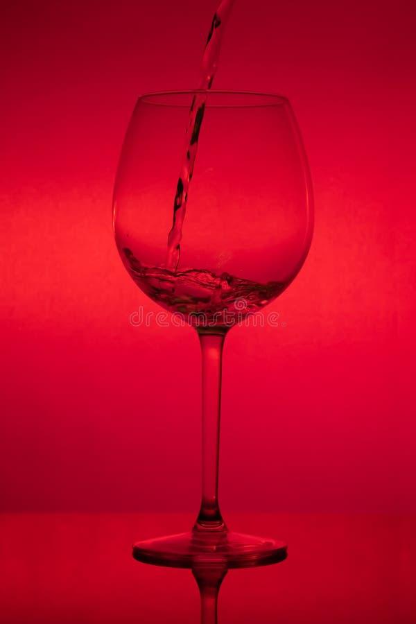 Γεμίζοντας το γυαλί, που χύνει wineglass στο κόκκινο υπόβαθρο στοκ φωτογραφίες με δικαίωμα ελεύθερης χρήσης