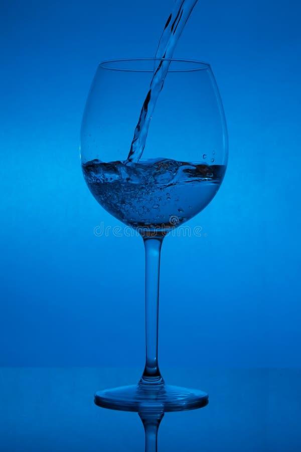 Γεμίζοντας το γυαλί, που χύνει wineglass στο μπλε υπόβαθρο στοκ εικόνα