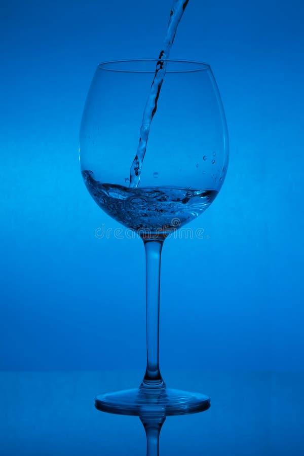 Γεμίζοντας το γυαλί, που χύνει wineglass στο μπλε υπόβαθρο στοκ φωτογραφία