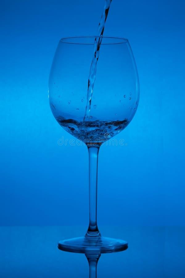 Γεμίζοντας το γυαλί, που χύνει wineglass στο μπλε υπόβαθρο στοκ εικόνες