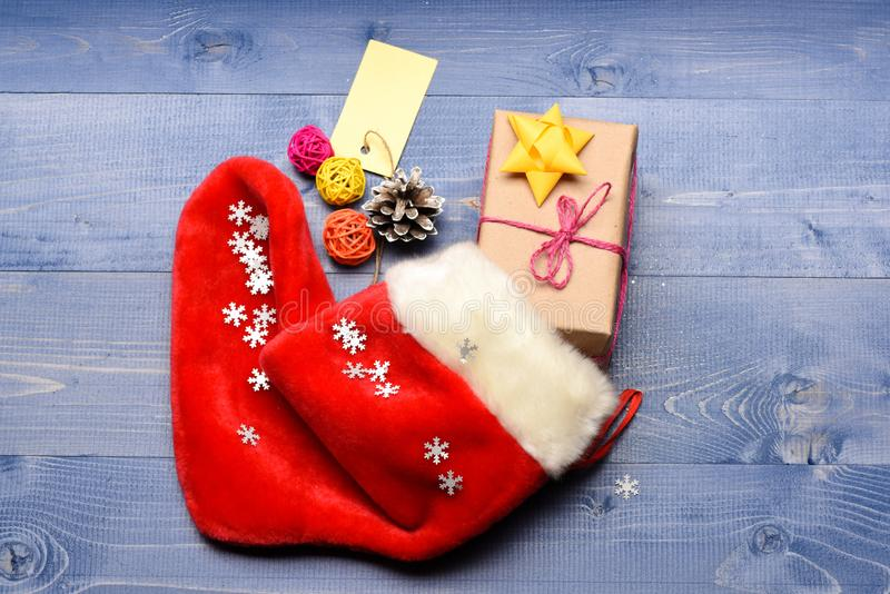 Γεμίστε την κάλτσα με τα δώρα ή παρουσιάζει Γιορτάστε τα Χριστούγεννα Περιεχόμενο της γυναικείας κάλτσας Χριστουγέννων Μικρά στοι στοκ εικόνα