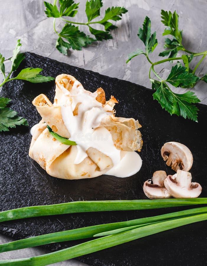 Γεμισμένος crepes ολοκληρωμένος με τη σάλτσα και τα πράσινα σουπών με κρέας μανιταριών στο πιάτο πέρα από τη σκοτεινή γκρίζα επιφ στοκ φωτογραφία με δικαίωμα ελεύθερης χρήσης