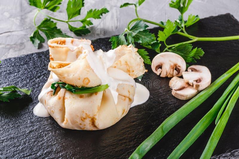 Γεμισμένος crepes ολοκληρωμένος με τη σάλτσα και τα πράσινα σουπών με κρέας μανιταριών στο πιάτο πέρα από τη σκοτεινή γκρίζα επιφ στοκ εικόνες