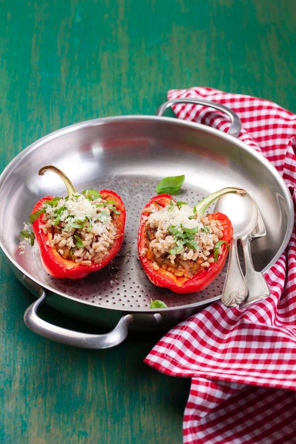 Γεμισμένο χορτοφάγο ή vegan γεμισμένο κόκκινο πιπέρι πάπρικας ή κουδουνιών με το συλλαβισμένο ή καφετί ρύζι και λαχανικά με το τυ στοκ φωτογραφία με δικαίωμα ελεύθερης χρήσης