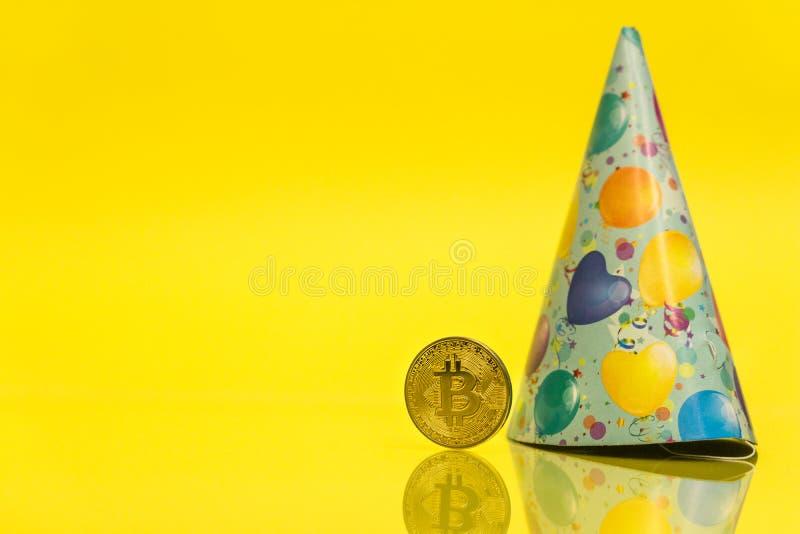 Γενέθλια εορτασμού cryptocurrency Bitcoin - 10 έτη, νόμισμα με το καπέλο γενεθλίων πίσω από το, με το κίτρινο διάστημα αντιγράφων στοκ εικόνα
