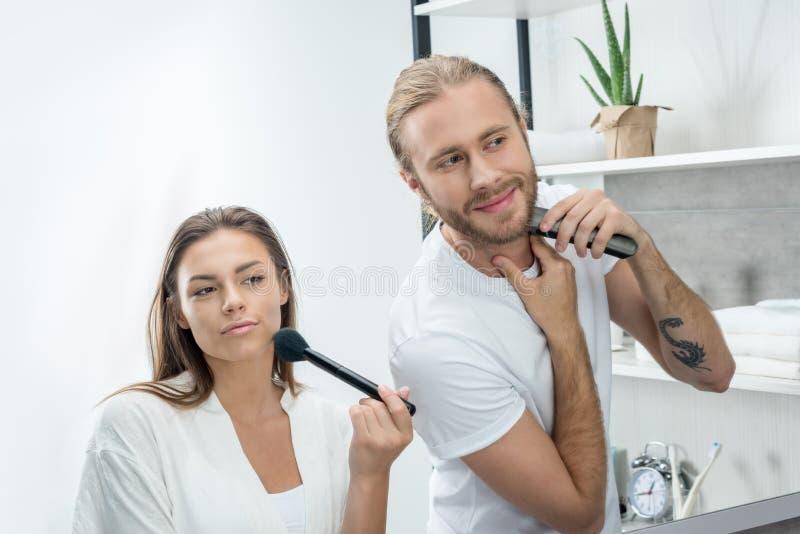 Γενειάδα ξυρίσματος ατόμων με trimmer ενώ σύζυγος που εφαρμόζει τη σκόνη προσώπου στοκ φωτογραφία