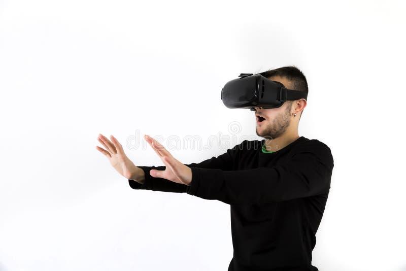 Γενειοφόροι νέος συμπαθητικός και σύγχρονος με τα γυαλιά vr που απολαμβάνουν την εικονική πραγματικότητα με τον προσομοιωτή στοκ φωτογραφία με δικαίωμα ελεύθερης χρήσης