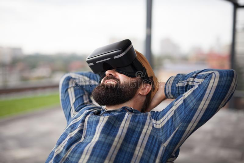 Γενειοφόρος άνδρας χρησιμοποιεί ακουστικά με γυαλιά εικονικής πραγματικότητας Φουτουριστικός προσομοιωτής στοκ εικόνες