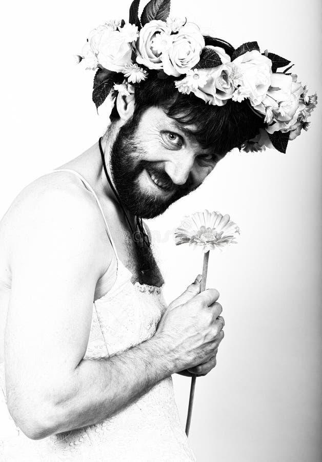 Γενειοφόρος άνδρας στο γαμήλιο φόρεμα μιας γυναίκας στο γυμνό σώμα της, που κρατά ένα λουλούδι Στο κεφάλι του ένα στεφάνι των λου στοκ εικόνες με δικαίωμα ελεύθερης χρήσης