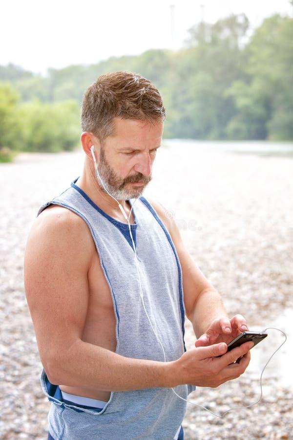 Γενειοφόρος αθλητής που εξετάζει υπαίθρια το τηλέφωνό του στοκ εικόνες με δικαίωμα ελεύθερης χρήσης