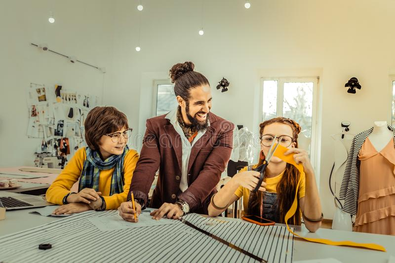 Γενειοφόρος δάσκαλος που αισθάνεται χαρούμενος συνεργαμένος με τους σπουδαστές του στοκ φωτογραφία