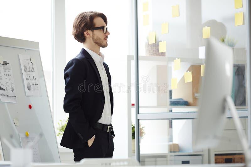 Γενειοφόρος διευθυντής που σκέφτεται πέρα από το πρόγραμμα στοκ εικόνα με δικαίωμα ελεύθερης χρήσης