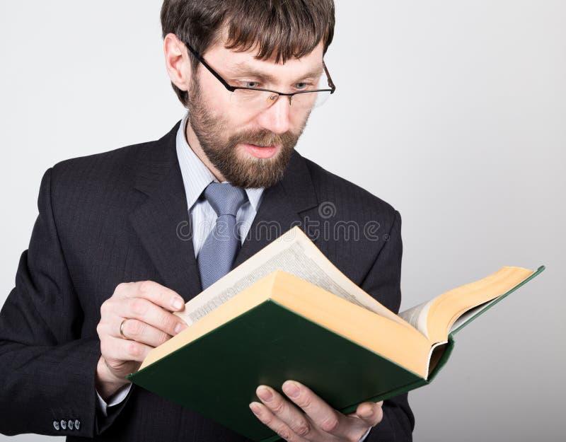 Γενειοφόρος επιχειρηματίας σε ένα επιχειρησιακό κοστούμι και έναν δεσμό, που διαβάζουν ένα παχύ βιβλίο στοκ εικόνα με δικαίωμα ελεύθερης χρήσης