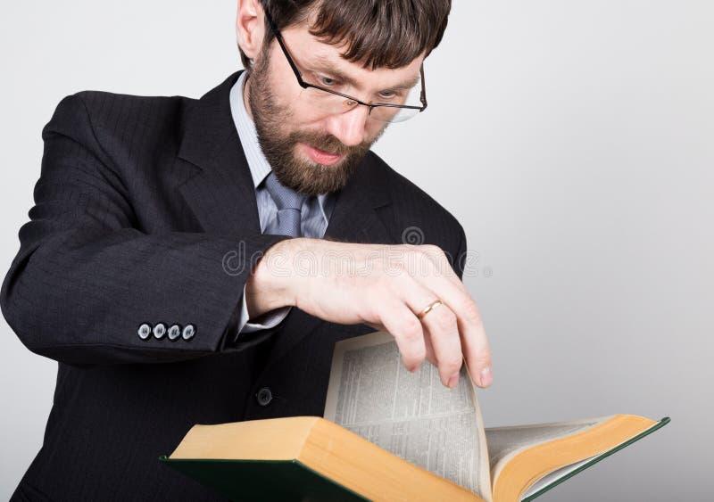 Γενειοφόρος επιχειρηματίας σε ένα επιχειρησιακό κοστούμι και έναν δεσμό, που διαβάζουν ένα παχύ βιβλίο στοκ εικόνα