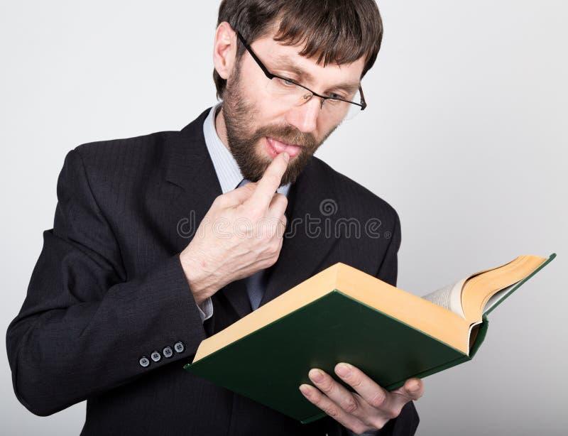 Γενειοφόρος επιχειρηματίας σε ένα επιχειρησιακό κοστούμι και έναν δεσμό, που διαβάζουν ένα παχύ βιβλίο στοκ φωτογραφίες