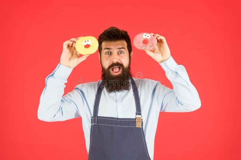 Γενειοφόρος λαβή αρτοποιών Hipster donuts Doughnut αρτοποιείο Βερνικωμένο doughnut Γενειοφόρο εύθυμο καλά καλλωπισμένο άτομο στην στοκ εικόνες
