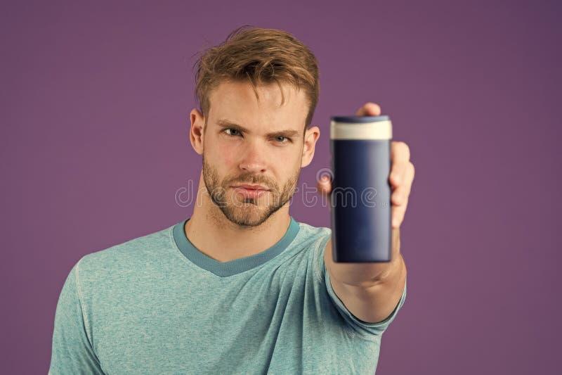 Γενειοφόρος μοντέρνος ατόμων κρατά το πλαστικό μπουκάλι Όμορφη προσοχή τύπων για το καλλυντικό ή υγιεινό προϊόν χρήσης εμφάνισης  στοκ εικόνα με δικαίωμα ελεύθερης χρήσης