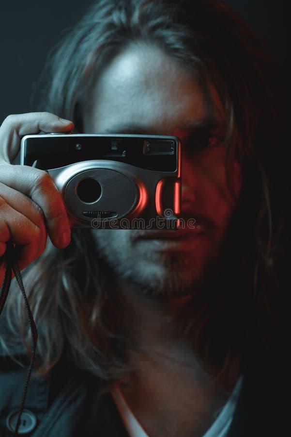 Γενειοφόρος νέα μακρυμάλλης ψηφιακή κάμερα εκμετάλλευσης ατόμων στοκ εικόνες
