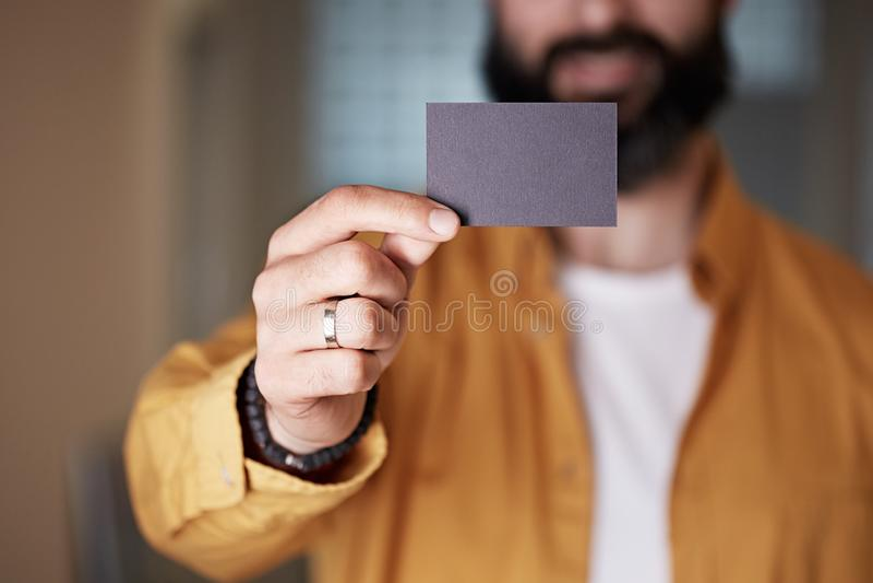 Γενειοφόρος νεαρός άνδρας που δίνει στο χέρι την κενή μαύρη επαγγελματική κάρτα στο θολωμένο υπόβαθρο Κενή διαφήμιση κολλών αντιγ στοκ εικόνες