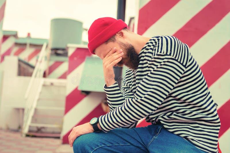 Γενειοφόρος νεαρός άνδρας που κλείνει τα μάτια του παίρνοντας κουρασμένος στοκ φωτογραφία