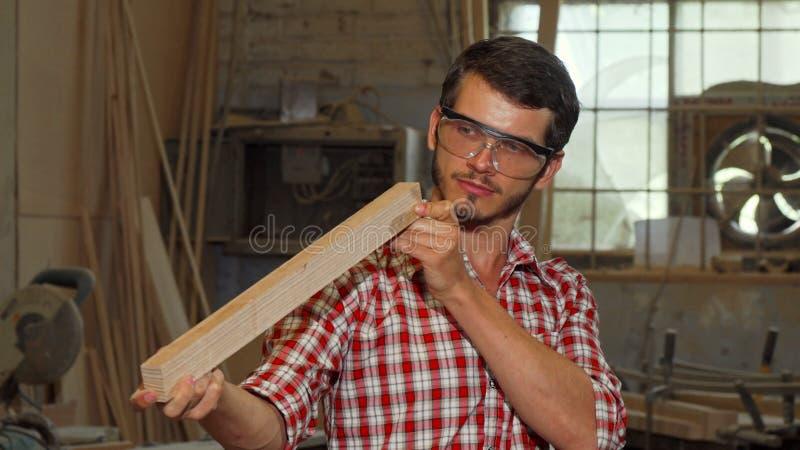Γενειοφόρος ξυλουργός που εξετάζει το ξύλινο κομμάτι μετά από να αλέσει το στοκ φωτογραφία με δικαίωμα ελεύθερης χρήσης