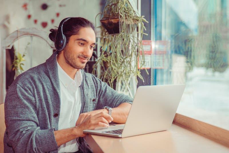 Γενειοφόρος σπουδαστής νεαρών άνδρων στον καφέ που χρησιμοποιεί το φορητό προσωπικό υπολογιστή και τη μουσική ακούσματος στοκ εικόνες με δικαίωμα ελεύθερης χρήσης