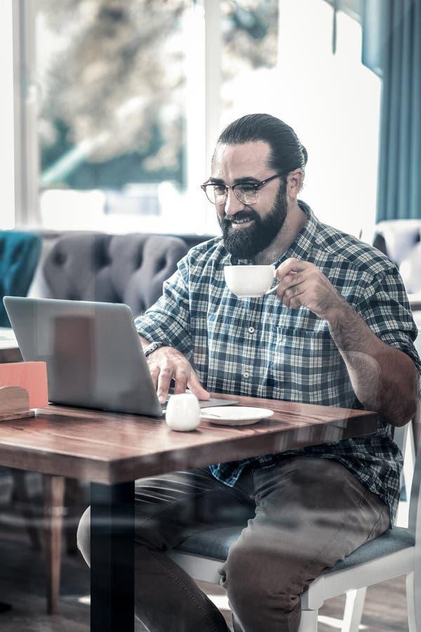 Γενειοφόρος συγγραφέας freelancer που εργάζεται στο lap-top του που έχει τον καφέ στοκ εικόνες με δικαίωμα ελεύθερης χρήσης