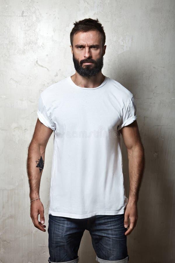 Γενειοφόρος τύπος που φορά την άσπρη κενή μπλούζα στοκ εικόνες