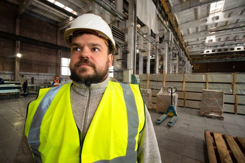 Γενειοφόρος όμορφος χαμογελώντας εργαζόμενος, κράνος και φανέλλα μηχανικών στοκ φωτογραφία