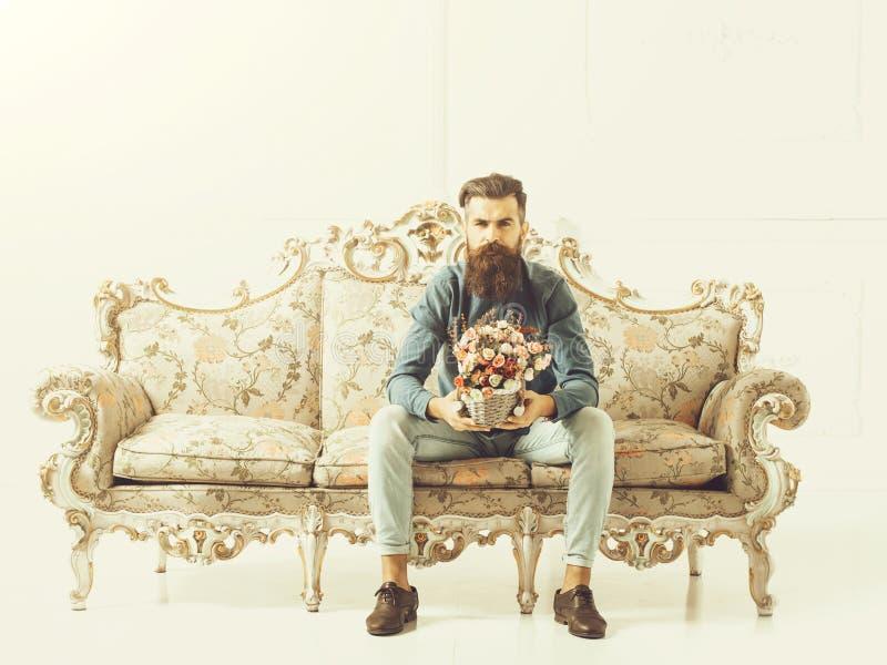 Γενειοφόρο άτομο με τα λουλούδια στον καναπέ στοκ φωτογραφίες