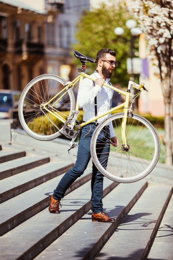 Γενειοφόρο άτομο με το ποδήλατο αποτυπώσεων Άποψη του βέβαιου νέου γενειοφόρου ατόμου που φέρνει το ποδήλατό του στον ώμο και που στοκ φωτογραφία