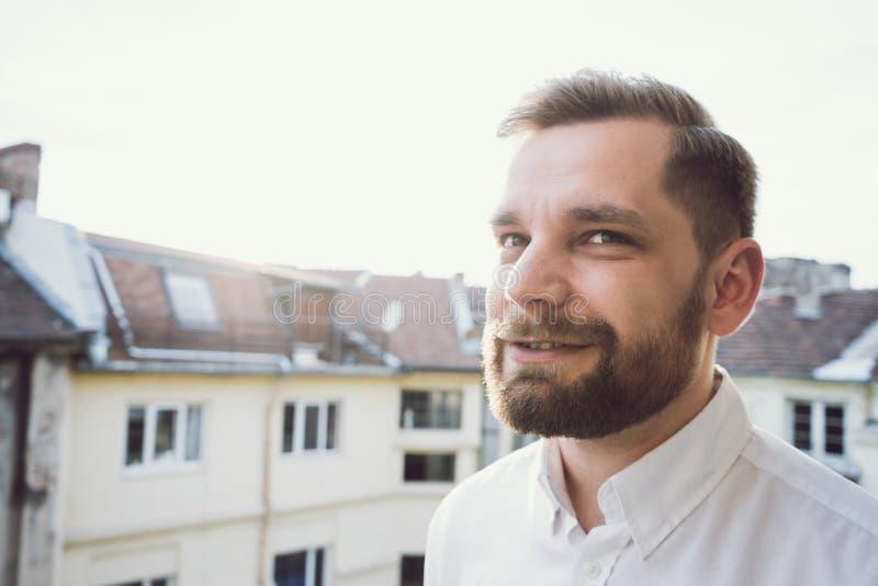 Γενειοφόρο άτομο που έχει μια συνομιλία που μιλά στο ηλιοβασίλεμα και το άσπρο πουκάμισο στοκ εικόνα