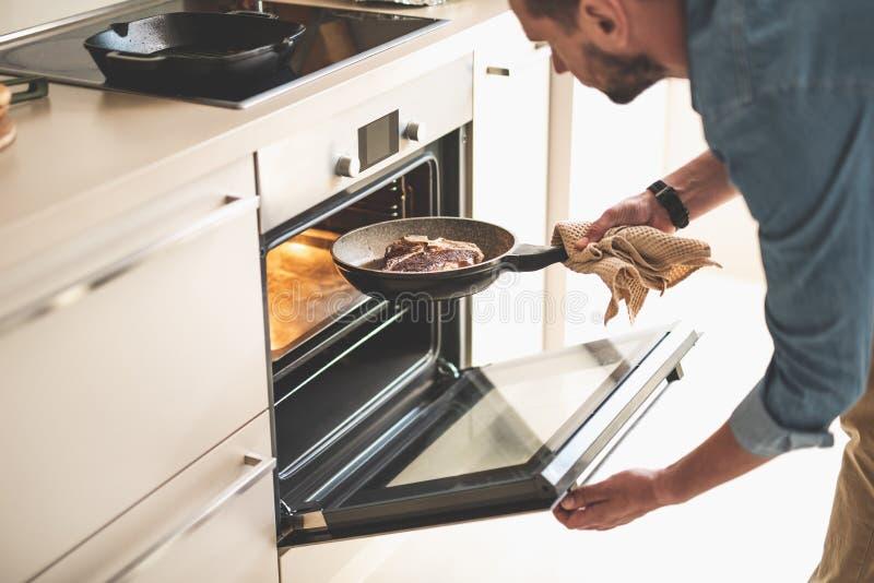 Γενειοφόρο άτομο που βάζει το κρέας στο φούρνο μαγειρεύοντας το γεύμα στοκ εικόνες με δικαίωμα ελεύθερης χρήσης